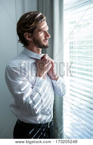 Man getting dressed while looking through window blinds at home