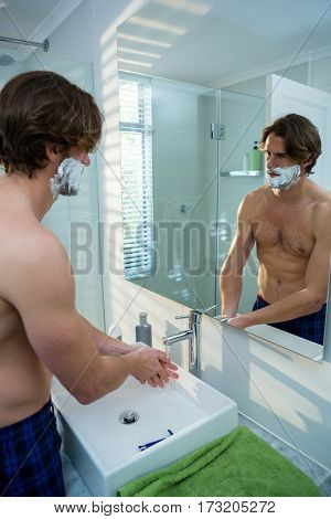 Man washing his hands in bathroom sink at home