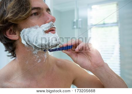 Close-up of man using a razor to shave his beard off in bathroom at home