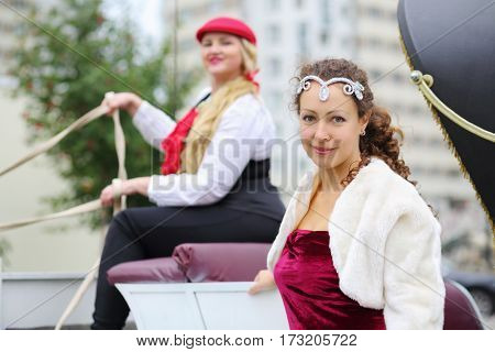 Happy woman poses near coach with coachman blonde near residential buildings, focus on woman in furcoat