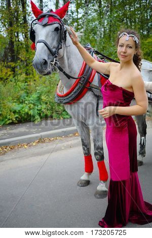 Pretty woman in red dress stands near horse in harness in green park