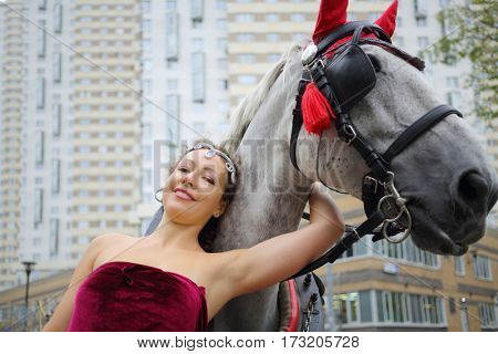 Happy woman in red dress stands near horse in harness near residential building