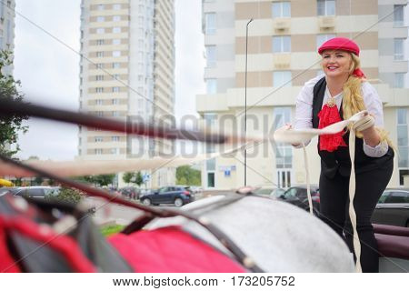 Coachman blonde holds reins on trestles of couch with horse near residential buildings