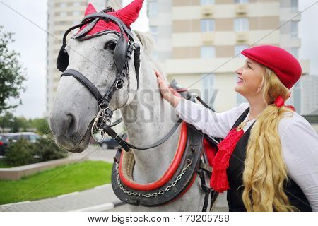 Coachman happy blonde stands with horse in red harness near residential buildings