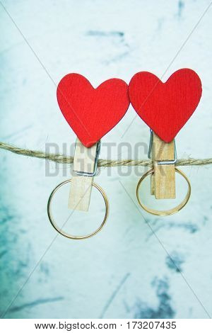 wedding concept: golden rings hanging on clothespins with hearts