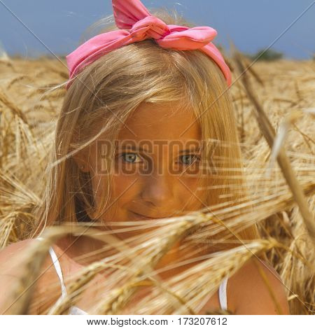 Youngl and happy blonde woman or teenage girl in a meadow of rye. (sunlight nature summer holiday vacation and people concept)