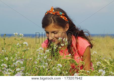 Close-up portrait of Beautiful young blonde girl enjoying nature. Happy Smiling female smell a flower with close eyes. (Pleasure nature travel vacation)