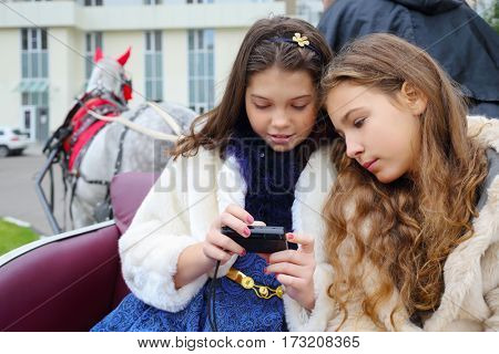 Two girls looks photos at camera in coach with coachman and horse near residential buildings