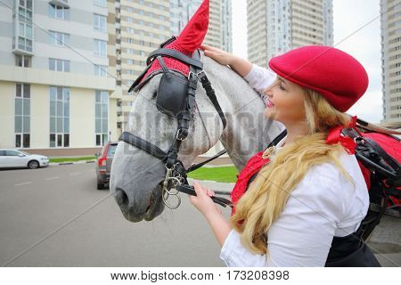 Coachman woman stands with horse in red harness near residential buildings