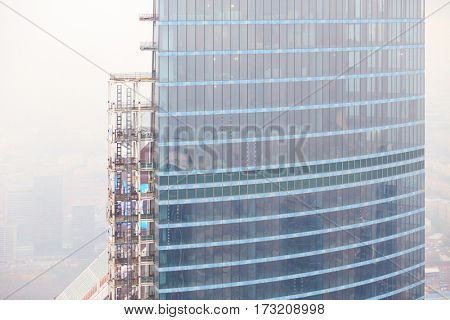 Part of high modern office building under construction among fog in city