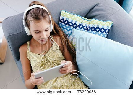 10 years old tween girl relaxing on a couch, listening to music in headphones and playing with tablet pc. Child chilling on the sofa in living room.