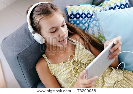 10 years old tween girl relaxing on a couch, listening to music in headphones and using tablet pc. Child chilling on the sofa in living room.