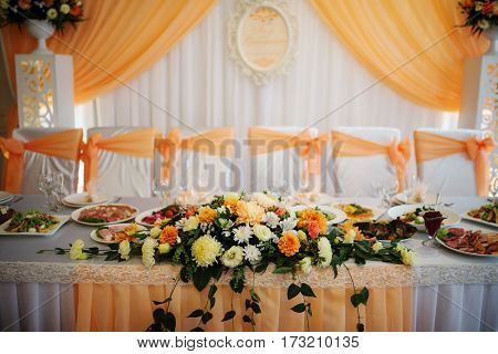 Orange Composition Of Flowers On Table Of Newlyweds.