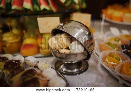 Orange And White Macarons At Steel Iron Casserole On Wedding Reception.