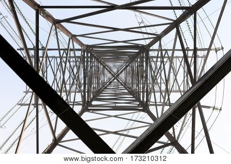 Metal construction of high-voltage support. View from the bottom up. Against the background of a gray misty sky.