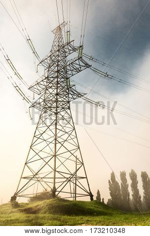 Support high-voltage electric line. View from the bottom up. Against the background of a gray misty sky.