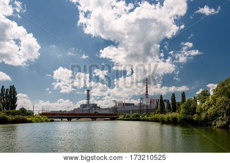 Kursk Nuclear Power Plant reflected in a calm water surface. Mist over the water.