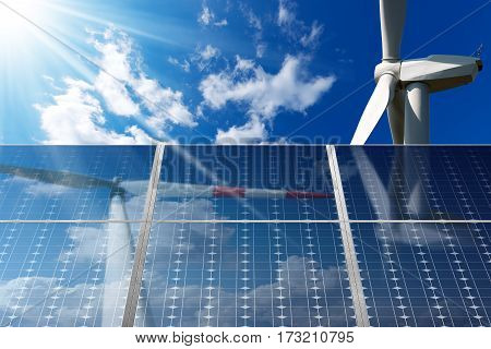 Solar panels and two wind turbines on a blue sky with clouds and sun rays. Solar and wind energy