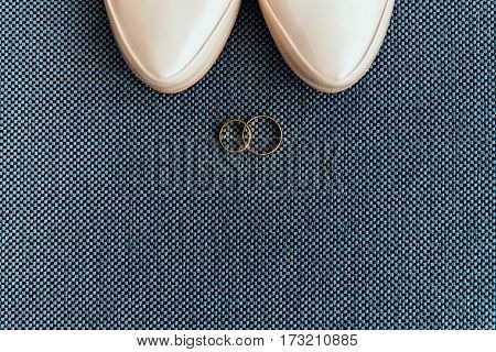 Shoes Of The Bride Near Wedding Rings