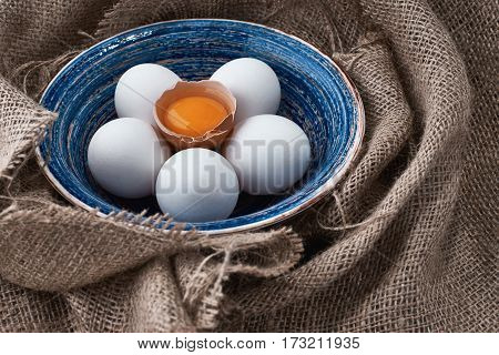 Ecological natural fresh eggs collected in the plate for cooking on the fabric.