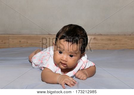 cute asian baby lying on bed in room