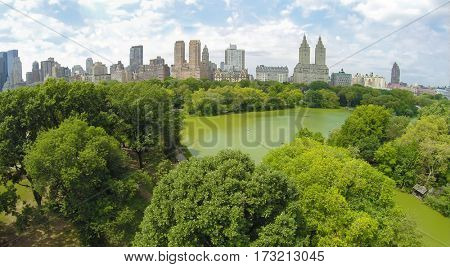 Central Park with The Lake among trees and city buildings at sunny summer day. Aerial view