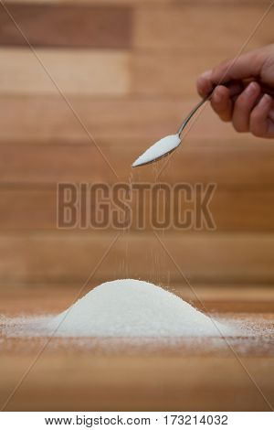 Woman hand pouring sugar from spoon on wooden table