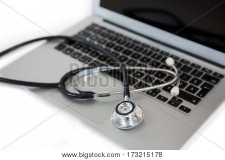 Close-up of stethoscope on laptop on white background