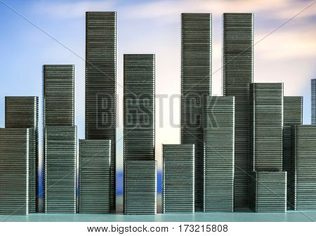 Staples arranged to form city skyline on a sunset background