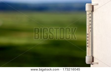 Thermometer Celsius Showing Warm Temperature On Blurred Green Ba