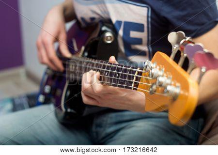 young man plays bass guitar close up