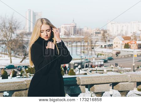 Young pretty blonde girl on city street