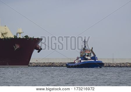 TUG AT WORK -  Large tug insures tanker in the harbor