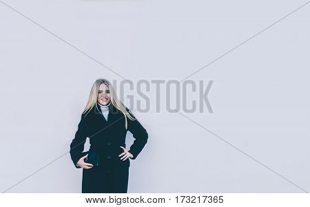 Young beautiful blonde girl near the building gray wall