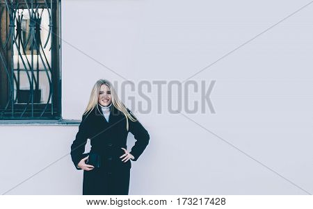 Young beautiful blonde girl near the building wall with windows