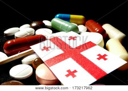 Georgian Flag With Lot Of Medical Pills Isolated On Black Background