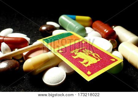 Sri Lankan Flag With Lot Of Medical Pills Isolated On Black Background