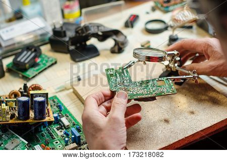 technician use third hand magnifier with a device for soldering