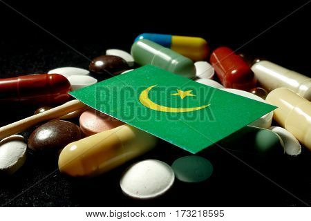 Mauritanian Flag With Lot Of Medical Pills Isolated On Black Background