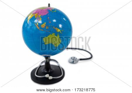 Close-up of world globe with stethoscope on white background