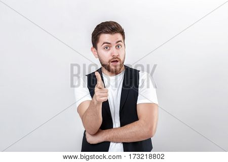 young handsome brunette man with a beard in a white shirt and a black waistcoat pointing forward and smiling