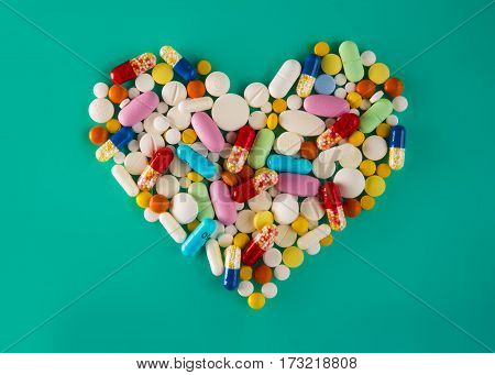 Multicolored Pills And Tablets, Heart Shape On Green Background