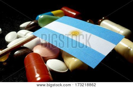 Argentine Flag With Lot Of Medical Pills Isolated On Black Background