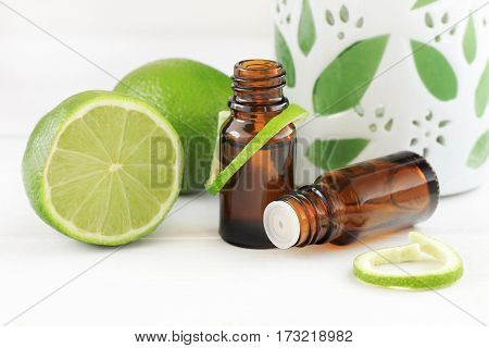 Lime essential oil. Fresh green fruit and rind, glass dropper bottles, aromalamp.