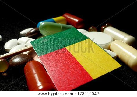 Benin Flag With Lot Of Medical Pills Isolated On Black Background