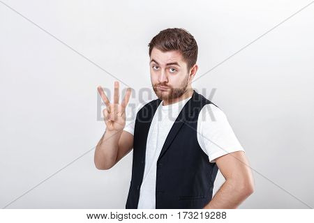 cute young man with a beard in a white shirt and a black waistcoat showing number three gesture