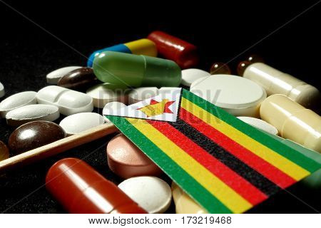 Zimbabwean Flag With Lot Of Medical Pills Isolated On Black Background