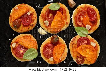 Mini home pizza with tomato and basil on baking tray, top view