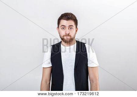 portrait of handsome young pensive brunette man in white shirt on gray background. guy thinks