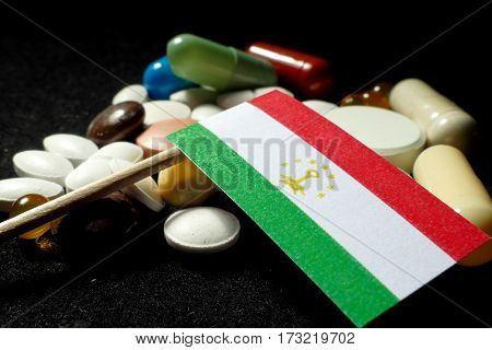 Tajikistan Flag With Lot Of Medical Pills Isolated On Black Background